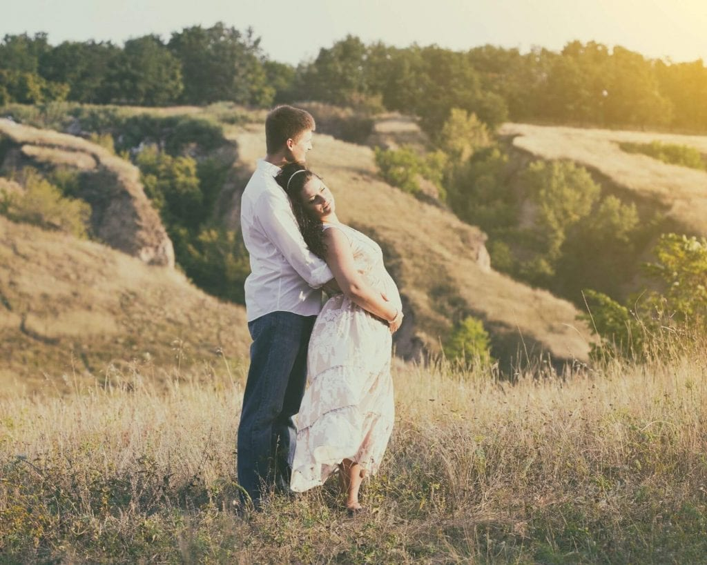 couple avec femme enceinte profitant du soleil d'une belle journée en nature