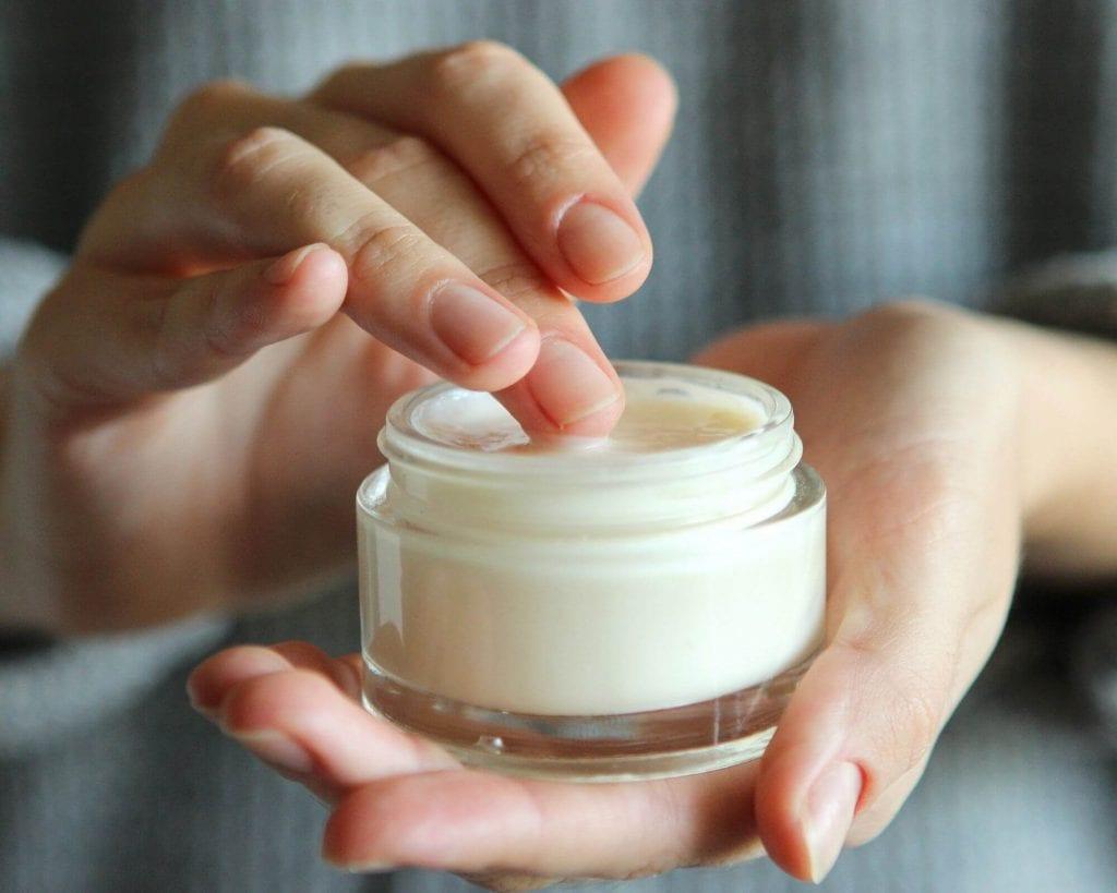 pot de crème hydratante pour le corps tenue par main de femme