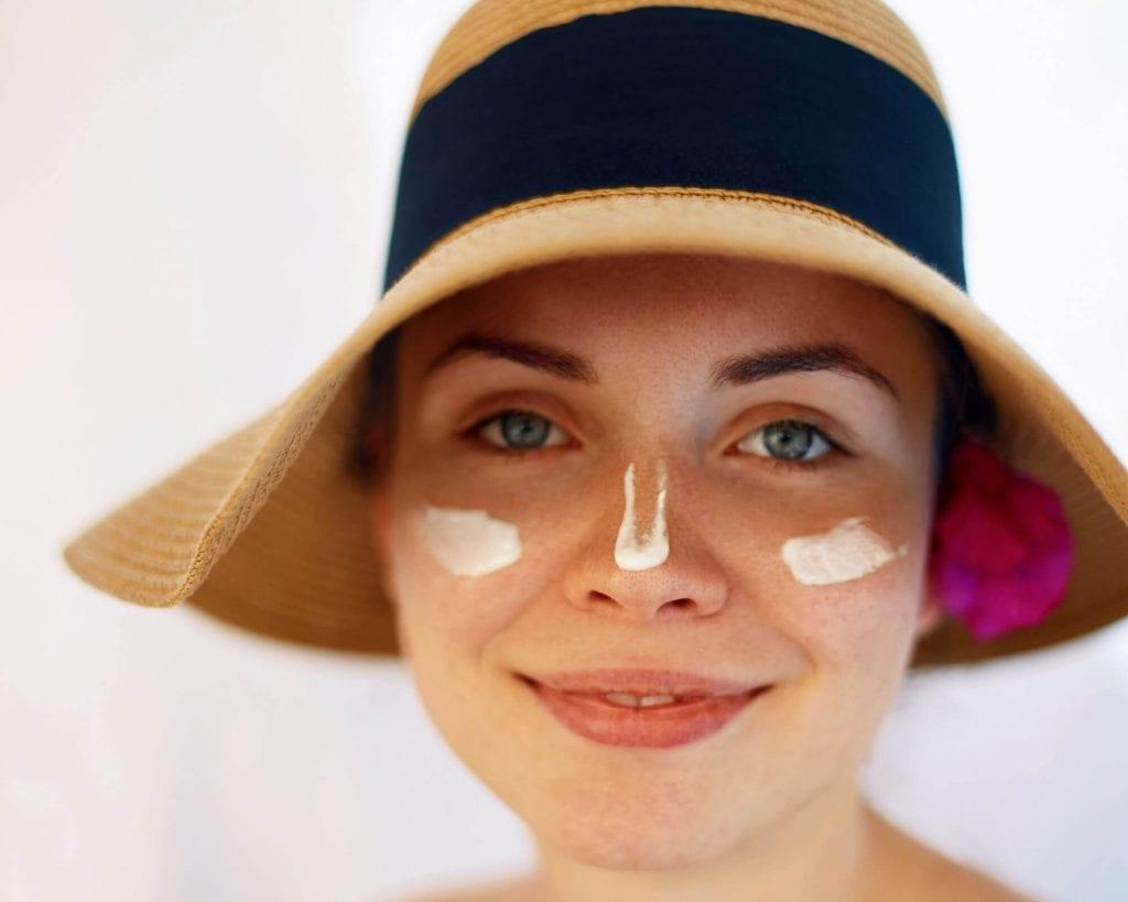 portrait de femme souriante avec chapeau larges bords et crème solaire